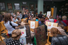 Folket deltar i det fria seminariet under den öppna dagen i vattenfärgskola Arkivbild