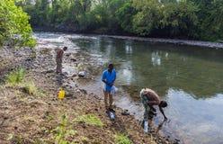 Folket drar vatten från Mago River till flaskor Omo dal Och Arkivbild