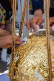 Folket försöker att klibba en guld- tjänstledighet på den begravde stenen när den thai tradien Royaltyfria Bilder