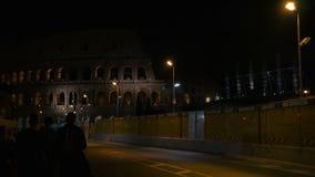 Folket flyttar sig in mot Colosseum på natten i Rome arkivfilmer