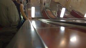 Folket flyttar sig ner på en rulltrappa i Moskvatunnelbana arkivfilmer