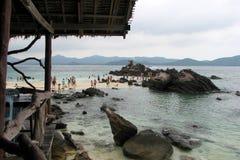Folket går i havet nära kusten som omges av enorma stenar mot bakgrunden av bergen, Thailand royaltyfria bilder