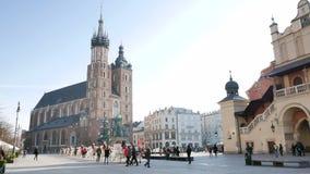 Folket går på den huvudsakliga marknadsfyrkanten i Krakow arkivfilmer