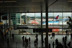 Folket går på genomresa område på den Schipol flygplatsen i Holland Arkivbild