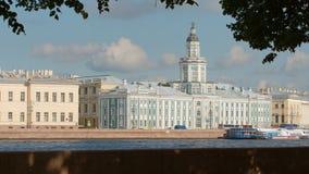 Folket går på invallningen av den Neva floden på den Kunstkamera bakgrunden Royaltyfri Foto