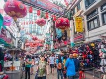Folket går till och med en upptagen Kina stad på den Petaling gatan, malajiskor Royaltyfri Bild