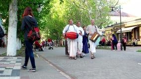 Folket går till staden tillbad Krishnaen, hareKrishna medlemmar av gruppen av klosterbrodertrender inom Vaishnavism stock video