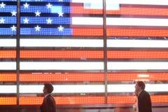 Folket går vid amerikanska flagganljus Time Square Arkivfoton