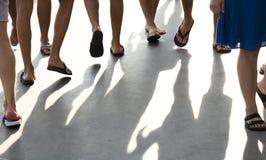Folket gör bar ben bläddrar in misslyckanden som går på strandpromenad arkivbild