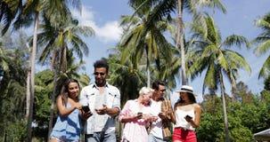 Folket grupperar talande brukscellSmart telefoner som utomhus går under palmträd, lycklig le blandningloppman och kvinna