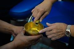 Folket häller ceremoniellt vatten och ber för det avlidet royaltyfri foto