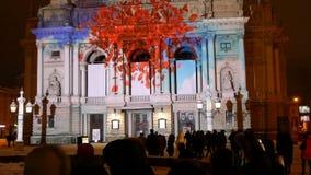 Folket håller ögonen på nattljusshowen på byggnaden av den Lviv operan stock video