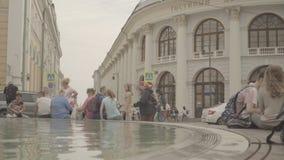 Folket har en vila runt om springbrunnen nära Gostinniyen Dvor i Moskva arkivfilmer