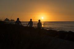 Folket i en kontur mot solnedgång tänder med solen på horisonten i bakgrunden Arkivfoton