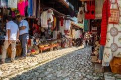 Folket i en medina gatamarknad med souvenir, hantverkobjekt och litet shoppar royaltyfria bilder