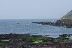 Folket i likformig på kusten och i fartyget för räddningsaktioner på seacoasna Arkivfoto