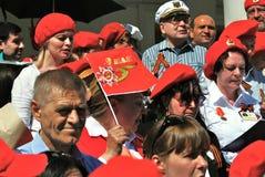 Folket i röda hattar sjunger krigsånger på Victory Day Royaltyfri Fotografi