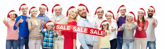 Folket i santa hattar med försäljning undertecknar på jul arkivbild
