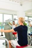 Folket i sportidrottshall på konditionen bearbetar med maskin Royaltyfria Foton