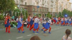 Folket i trevliga dräkter dansar i gatan som roar folk i stad på stadsdag lager videofilmer