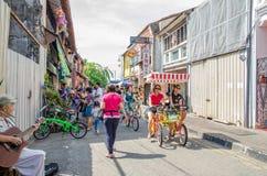 Folket kan sett gå och undersökning runt om gatakonsten i Georgetown, Penang Arkivfoton