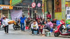Folket kan sett ha deras mat bredvid gatan för Hanoi ` s Arkivfoton