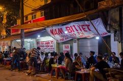 Folket kan sett tycka om deras mat på matstallsna i Hanoi, Vietnam Arkivbilder