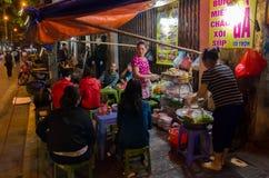 Folket kan sett tycka om deras mat på matstallsna i Hanoi, Vietnam Royaltyfri Fotografi