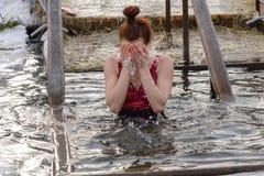 Folket kasta sig in i ett ishål under den ortodoxa festmåltiden av epiphanyen Royaltyfri Bild