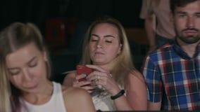 Folket kommer i konserthall sitter i stolar som erfar olika sinnesrörelser arkivfilmer