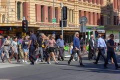 Folket korsar gatan framme av byggnad för Flindersdrevstationen i Melbourne Arkivbild
