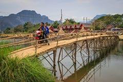 Folket korsar träbron på Mekonget River i byn av Vang Vieng arkivfoto