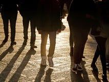 Folket lägger benen på ryggen att gå i staden på solnedgången Arkivfoton