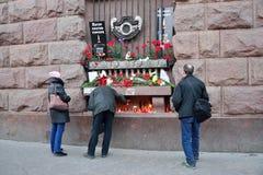 Folket lägger blommor i minnet av offren av terroristen att Royaltyfri Foto