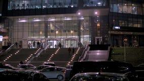 Folket lämnar affärsmitten, efter arbete, i aftonen Rörelsen av bilar och taxi stock video