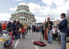 """Folket lyssnar musik på gatan nära vid domkyrkaSt Aleksander Nevsky i Sofia, Bulgarien†""""april 9, 2017 arkivfoto"""