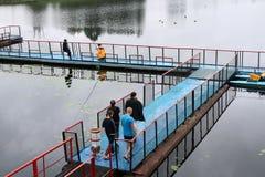Folket män fiskar från ponton, förklädet, bro på sjön med änder på rekreationmitten, sanatorier i nedgången royaltyfri foto