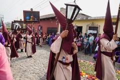 Folket med den spetsiga huven kostymerar bärande målningar av vägen av korset på processionen av San Bartolome de Fotografering för Bildbyråer