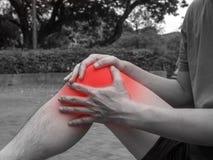 Folket med knäet smärtar, och den kännande dåliga handen på knäa han, det sunda begreppet fotografering för bildbyråer