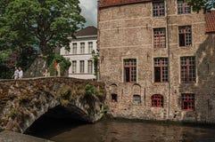 Folket och gamla byggnader på kanal`en s kantar på Bruges Arkivfoto