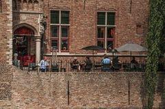 Folket och gamla byggnader på kanal`en s kantar på Bruges Arkivfoton