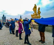 Folket organiserade en bosatt kedja på Charles Bridge i Prague royaltyfria foton