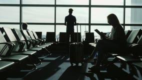 Folket på flygplatsterminalen väntar på flyget Använd apparater som ser till och med fönstren på flygfältet och arkivfoto