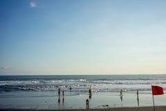 Folket på havet sätter på land med vågor och varningsflaggan royaltyfria foton