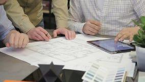 Folket på tabellen diskuterar projekt på papper och arbetar på minnestavlan lager videofilmer