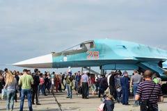 Folket på utställningen, betraktar en modern rysk stridsflygplan su-34 fotografering för bildbyråer