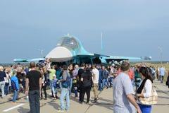 Folket på utställningen, betraktar en modern rysk stridsflygplan su-34 arkivbild