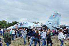 Folket på utställningen, betraktar en modern rysk stridsflygplan su-27 arkivbild