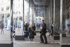 Folket passerar till och med ett spegelförsett hall på den Covent trädgården Arkivfoto
