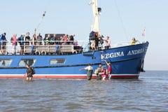 Folket passerar waysidemomenten för att gå till och med vattnet in mot den Wadden ön Griend Fotografering för Bildbyråer
